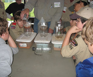 Boy Scouts learn about water infiltration using three different soil types at the Hornaday Award Weekend held at Camp Bovay near Navasota, Texas.