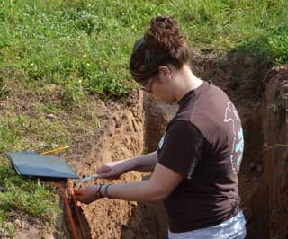 A student samples the subsoil to determine its permeability.