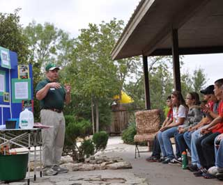 Ron Knight (left) explains the effects of using native plants in your landscape during the Runnels Soil and Water Conservation District's Natural Resource Day.