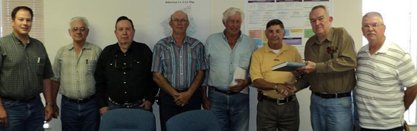 Robertson SWCD Directors are presented with the hard bound Soil Survey Manuscript by Soil Scientists: (From left to right) Dennis Brezina, Joe Stratta, Jerry Conn, Donald Bumpurs, Jim Steakley, John Sanders, Harold Hyde and Maurice Jurena.