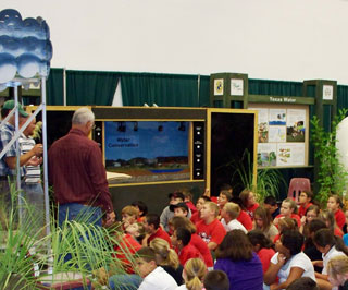 Elementary students listen as NRCS employees explain the benefits of conserving our natural resources and becoming good land stewards.
