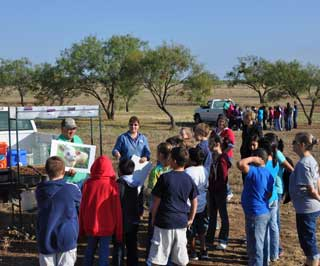 Natural Resources Conservation Service (NRCS) employees Charles Frerich and Kathy Saunders explain the effects of soil and wind erosion to a group of eager 5th grade students during the recent Natural Resource Day.