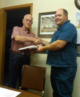 Sidney Paulson (right) presents Nathan Shack (chairman of the Young Soil and Water Conservation District Board) a leather-bound copy of Young County Soil Survey.
