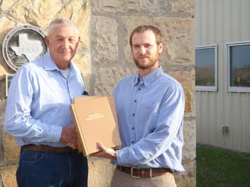 Larry Miles, Chairman of the McMullen County SWCD (left), is presented with the McMullen County Soil Survey manuscript from Clark Harshbarger, MLRA Project Leader NRCS Texas.