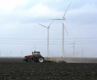 A familiar scene in San Patricio County is an agricultural producer preparing fields under the towering wind turbines that provide electricity for more than 54,000 homes on the Papalote Creek Wind Farm.