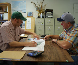 David Manthei, (left), NRCS district conservationist in Anahuac goes over Migratory Bird Habitat Initiative contracts with Will Beaty of Chambers County. Beaty has enrolled more than 2,000 acres into the agency�s initiative.