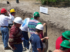 Soil scientists, in accordance with OSHA regulations, wearing hard hats in a soil pit.