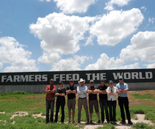 The Nuffield Scholars at Harry DeWitt�s High Plains Dairy barn that proudly proclaims �Farmers Feed the World.�