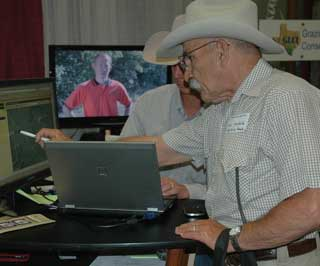 With a video about prescribed burns in Texas and Oklahoma playing in the background, a rancher points out his operation to Kevin Derzapf, GLCI Grazing Lands Specialist in Weatherford, during a discussion utilizing the Web Soil Survey at the 135th Annual TSCRA Convention held in Fort Worth this year.