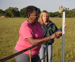 Kather Woods has been working with NRCS staff in Houston County for the last 19 years. Here she visits with soil conservationist Angie Osborn about conservation options on her land.
