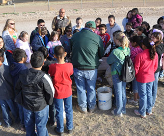 NRCS District Conservationist, Kyle Wright, explains how soil is made, its contents and gives a basic analysis during the Belding Farms Annual 5th Grade Field Day.