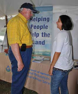 Samantha Valdez, NRCS district conservationist in Franklin, visits with Jim McCord of Bryan who is a director for the Brazos Area Hay Producers Association.