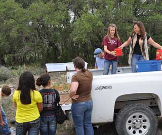 Mondee Edwards (right) hands water to a Sonora 6th grade student.
