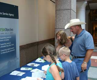 Ryan and Dana Hamilton and their children, Avery and Beck from Denton County, visit the NRCS and FSA booths at the Texas State Capitol to learn more about the USDA agencies and the 150th anniversary.