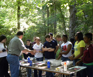Brezina demonstrating soil texture to Longview High School students at the Forestry Awareness Tour.