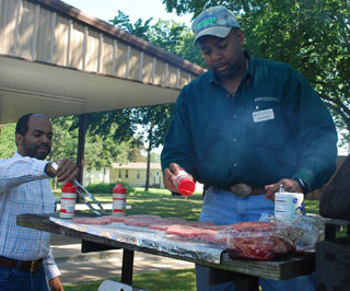 Delwin Cannon, NRCS soil conservationist (left) and Floyd Nauls, NRCS district conservationist, prepare lunch for attendees before traveling to a nearby ranch for the afternoon sessions.