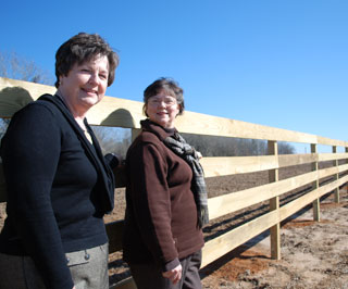 Janet Shrewsbury and Jane Ray standing at perimeter fence.