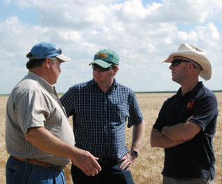 NRCS civil engineer Greg Sokora discusses various water-efficient irrigation methods with Australian farmers Alan Redfern and Brad Stillard.