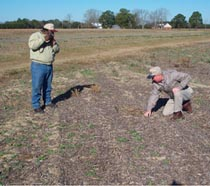 District Conservationist with Camera documenting crop residue.