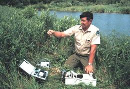 A field technician testing water drawn from a pond