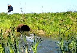A landowner adjusting the outflow of a water control structure to regulate the water level of a wetland
