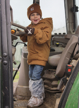 Web image: A Bugbee student sits in the cab of a John Deere tractor at the end of the farm tour