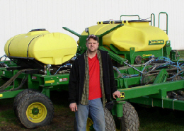 Web image: Andy Milleville standing beside new farm equipment that allows him to perform no-till plantings on heavy soils. Click image for full screen view