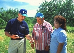 An NRCS representative reviewing a conservation plan with landowners