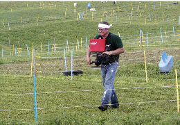 A farmer using a hand seeder to distribute seed in a paddock of a rotational grazing system