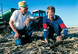 Web image: Photo of landusers inspecting crop residue remaining on a field as part of a pest management program