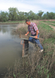 Web image: Photo of a landuser adjusting a device that controls the water level in the wetland. Click photo for full page view