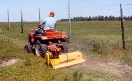 A small garden tractor with a mowing attachment being used to manage brush growth
