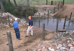 Web image: Photo of a fence that restricts livestock to a concrete stream crossing installed for their use. Click photo for full page view