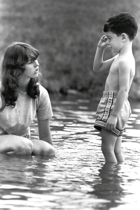 Web image: Photo of a swimming instructor coaxing a reluctant student into the water. Click photo for full page view.