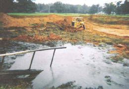 A bulldozer removing an inground waste storage facility