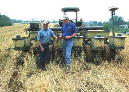 Web image: Photo of an NRCS District Conservationist and landuser discussing farm planning and no-till planting of corn into a cover crop of barley. Click photo for full screen view
