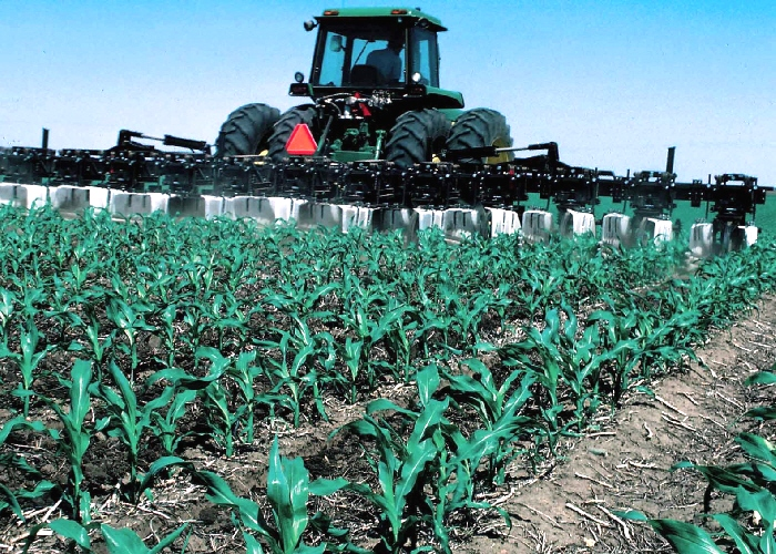 A tractor working in a field of corn where residue and tillage management are in practice