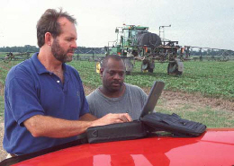 Web image: Photo of a farmer providing on-farm energy use data to be entered into a computer