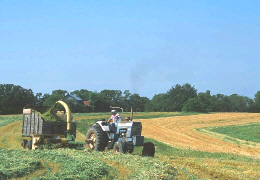 Photo of a farmer harvesting hay from a field is being farmed along the contour of the land. Click photo for full page view