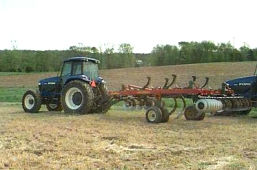 A farm tractor pulling a chisel implement that reaches depths of six to twelve inches.