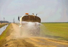 A tanker truck applying water to an unpaved surface
