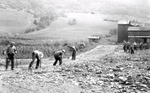 Web image: Photo of workers cleaning up gravel fan on a meadow. Hartsville, Stuben County, New York. August 1935. Click photo for full page view.