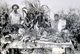 Web image: Photo of a farm family proudly displaying their harvest. Click photo for full page view