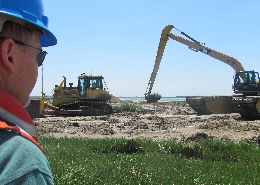 Web image: Stakeholder from the New York State Department of Environmental Conservation watches hummock removal process. Click image for full screen view