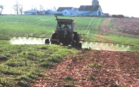 A farm tractor pulling a sprayer across a field.