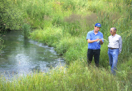 Web image: Photo of an NRCS representative and a landuser examining an area of a creek that has been rehabilitated. Click photo for full page view