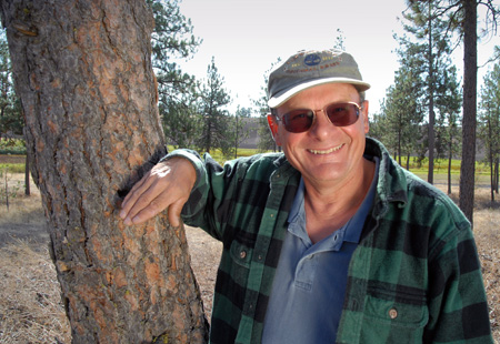 Ed Daellenbach pictured leaning against a tree, talking about his forest accomplishments.