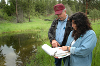Resource conservationist Patrice Beckwith (right) and John Hamilton review the progress of the habitat activities laid out in the conservation plan, which was developed for the project.