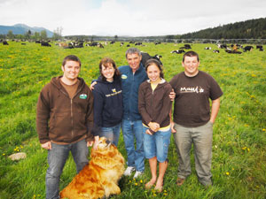Schmid family photo with their dog, standing with their organic farm cows