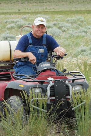 No longer able to walk fence lines, Gerald Davis now performs many of his farming chores via his four-wheel off-road vehicle.